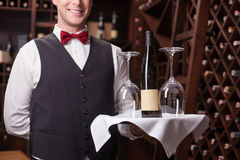 Cheerful male waiter is working in winehouse. Skillful young sommelier is serving a bottle of wine and wineglasses to the customer. He is standing and holding a royalty free stock photos