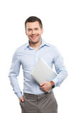 Cheerful male worker is holding a notebook. Portrait of smart businessman carrying a laptop. He is standing and smiling. Isolated Royalty Free Stock Photo
