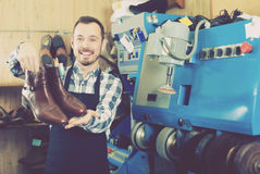 Cheerful male worker showing fixed shoes. In shoe repair workshop royalty free stock photo