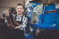 Cheerful male worker showing fixed shoes. In shoe repair workshop stock photo