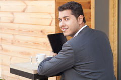 Cheerful male worker is using laptop in cafe. Attractive young businessman is sitting at table in cafeteria outdoors. He is holding tablet in his hands. The man Royalty Free Stock Photos