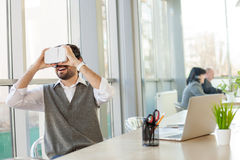 Cheerful male worker is using modern technology. Happy young man is wearing virtual reality glasses. He is sitting at the desk in his office and smiling Stock Photos