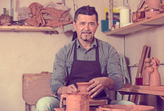 Cheerful male working with clay on pottery wheel. Portrait of cheerful male potter working with clay on pottery wheel in atelier royalty free stock photo