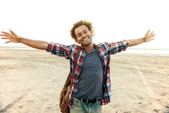 Cheerful man with arms spread opened standing at the beach Stock Images