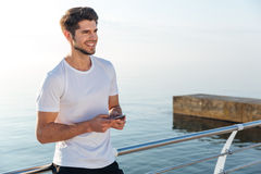 Cheerful man athlete in white t-shirt using cell phone Stock Image