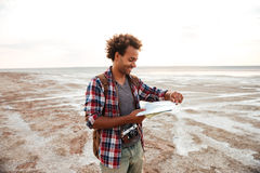 Cheerful man with backpack standing and examening map outdoors Royalty Free Stock Image