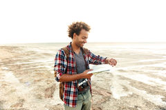 Cheerful man with backpack standing and examening map outdoors Stock Image