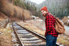 Cheerful man with backpack walking along railroad in mountains. Cheerful attractive bearded young man with backpack walking along railroad in mountains Royalty Free Stock Photography