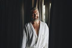 Cheerful man in a bathrobe royalty free stock images