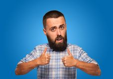 Cheerful man with a big funny head holding a thumbs up. Cheerful beard man with big funny head holds a thumbs up on a blue isolated background stock image