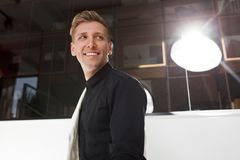 Cheerful man in black shirt. Handsome smiling man in black shirt looking away in backlit Stock Photos