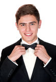 Cheerful man in a black suit adjusts his bow tie Royalty Free Stock Image