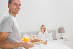 Cheerful man bringing breakfast in bed to his partner Royalty Free Stock Images