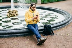 Cheerful man in cap, eyeglasses and yellow anorak sitting near fountain chatting with friends using mobile phone. Tired man after stock image