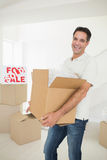 Cheerful man carrying boxes in a new house Royalty Free Stock Image