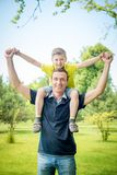 Cheerful man carrying his son on back against park. Portrait of a cheerful men carrying his son on back against park stock photos