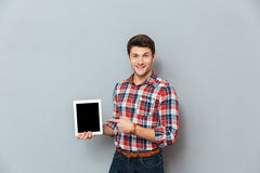 Cheerful man in checkered shirt pointing on blank screen tablet. Cheerful young man in checkered shirt pointing on blank screen tablet over grey background Stock Image