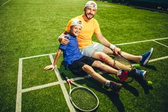Cheerful man and child relaxing after training royalty free stock images