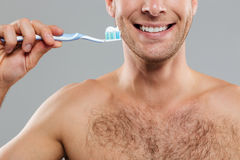 Cheerful man cleaning teeth by toothbrush with toothpaste and smiling. Cheerful young man cleaning teeth by toothbrush with toothpaste and smiling over grey Stock Photos