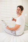 Cheerful man with coffee cup reading newspaper in bed Royalty Free Stock Image