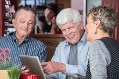 Cheerful Man in Coffee House using Tablet Computer Stock Images