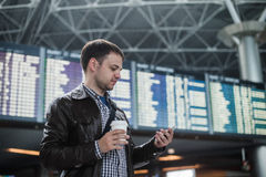 Cheerful man with coffee on the mobile phone in front of Board schedules in airport terminal Royalty Free Stock Photo