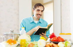 Cheerful man cooking   with cookbook Royalty Free Stock Photography