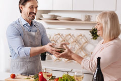 Cheerful man cooking salad with his mother in the kitchen Royalty Free Stock Photography