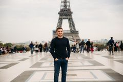 Cheerful man in dark blue pullover is standing on the background of the Eiffel Tower stock image