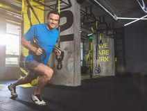 Cheerful man doing workout with suspension cable. Full length portrait of beaming male athlete taking exercise with trx while situating in gym. He looking at royalty free stock photos