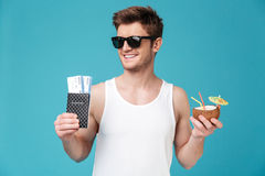 Cheerful man drinking cocktail holding tickets. Photo of young cheerful man standing over blue isolated background. Looking aside drinking cocktail holding Royalty Free Stock Image
