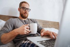 Cheerful man drinking coffee and working with laptop in bed Royalty Free Stock Photo