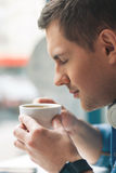 Cheerful man is drinking hot beverage Stock Images