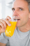 Cheerful man drinking orange juice in kitchen. Looking at camera Stock Photography