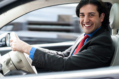 Cheerful man driving his new luxurious car Stock Image