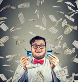 Cheerful man excited with money bonus. Young chunky man ended up with debts excited with successful reward looking excitedly at camera Royalty Free Stock Photos
