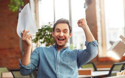 Cheerful man expressing jubilation. On the edge of emotions. Delighted overwhelmed man sitting at the table and holding hands up while feeling glad stock image