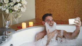 Cheerful man with foam on beard is taking selfie using smartphone in hot tub in modern spa salon. He is laughing
