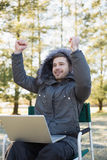 Cheerful man in fur hood jacket with laptop clenching fists in forest Stock Image