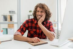 Inspired designer. Cheerful man getting inspired by workplace while brainstorming about new ideas Royalty Free Stock Photography