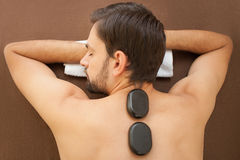 Cheerful man is getting treatment at spa Royalty Free Stock Image