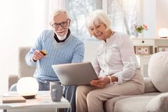 Cheerful man giving his bank card to make online payment. Fast payment. Cheerful senior men handing his credit card to his wife while they looking through an Royalty Free Stock Image