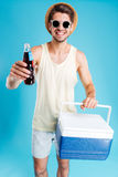 Cheerful man giving you cooling bag and bottle of soda Stock Photography