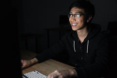 Cheerful man in glasses using laptop in dark room Stock Image