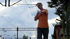 A cheerful man goes along a railroad platform in summer in slo-mo. A young man with a crew haircut smiles and goes along the railroad platform in Ukraine on a stock video