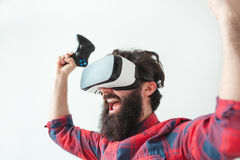 Cheerful man with hands up playing VR Stock Image
