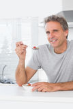 Cheerful man having cereal for breakfast in kitchen Stock Photos
