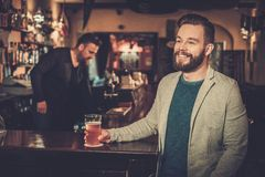 Cheerful man having fun watching a football game on TV and drinking draft beer at bar counter in pub. Stock Photos