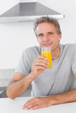 Cheerful man having glass of orange juice in kitchen Stock Image