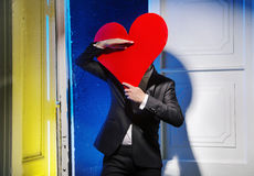 Cheerful man hiding himself behind a heart Royalty Free Stock Image